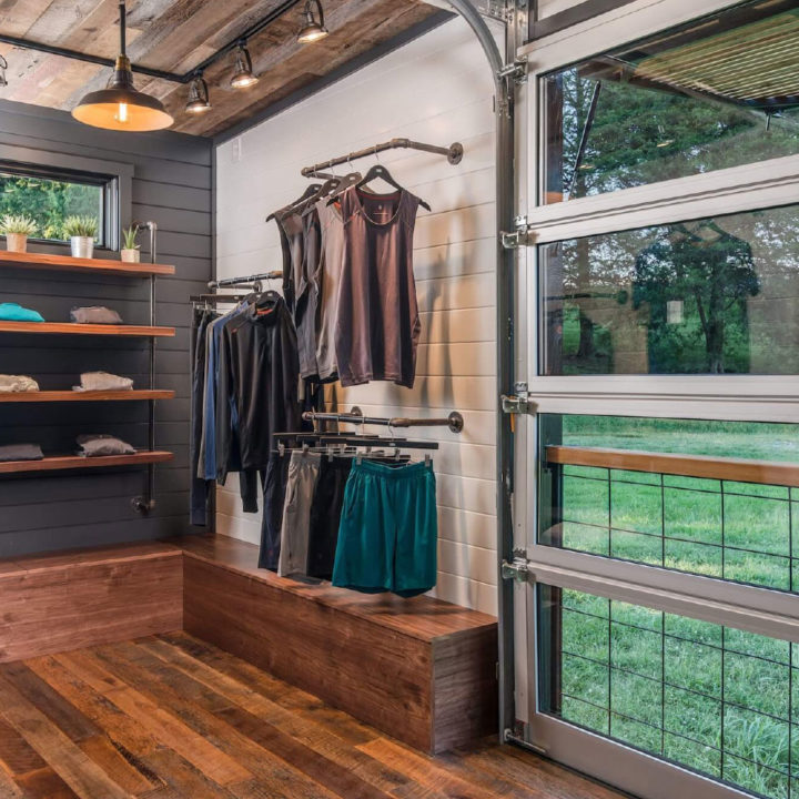 rhone tiny home interior with glass garage door and hanging clothes