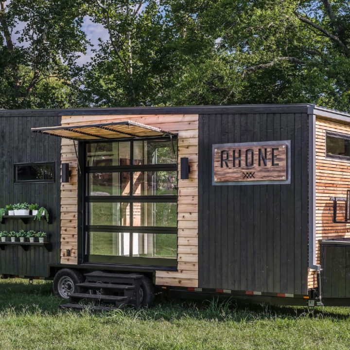 Exterior of rhone tiny home with glass garage door and logo