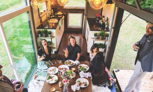 Image of smiling friends at a dinner table in a tiny house