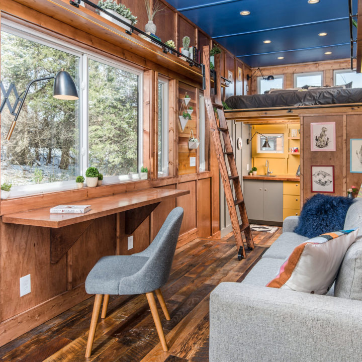 Interior of cornelia tiny house with sofa and loft bed and wood ladder