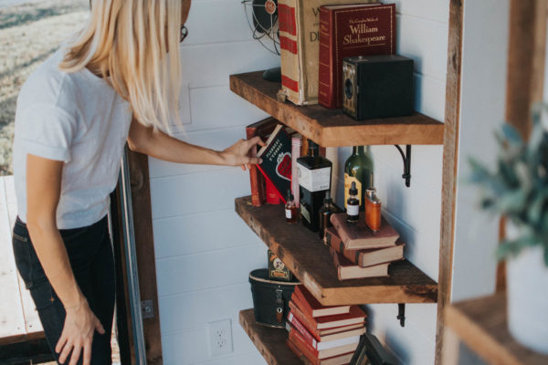 Woman looking at books on a tiny home shelf