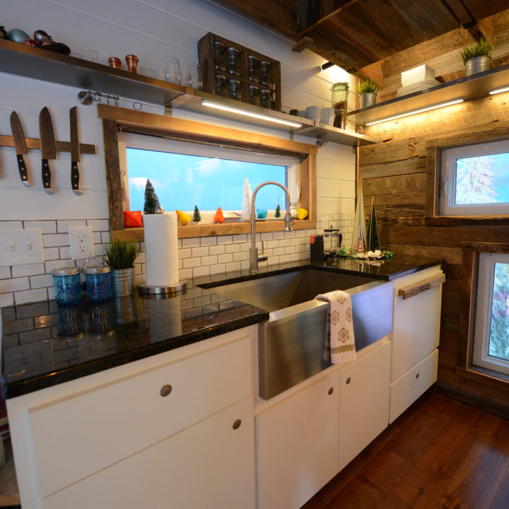 tiny house kitchen with big sink and snowy trees out window
