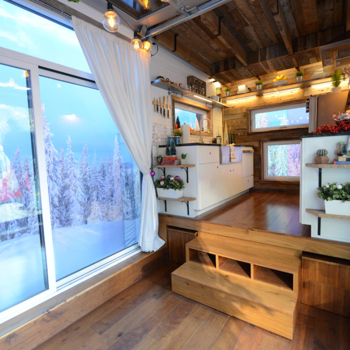 Interior of tiny house with very snowy view out of glass windows