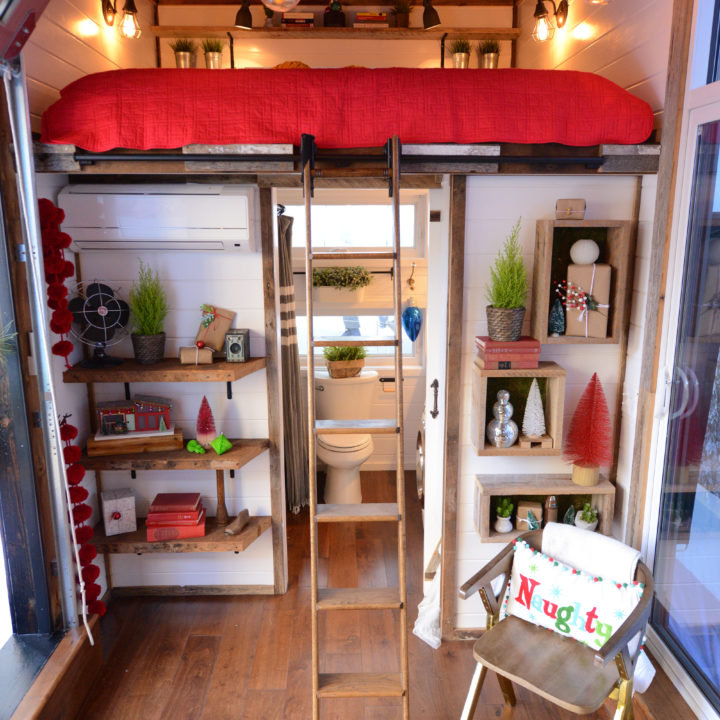 interior shot of tiny home with stairs centered on loft railing leading up to red bed and mistletoe