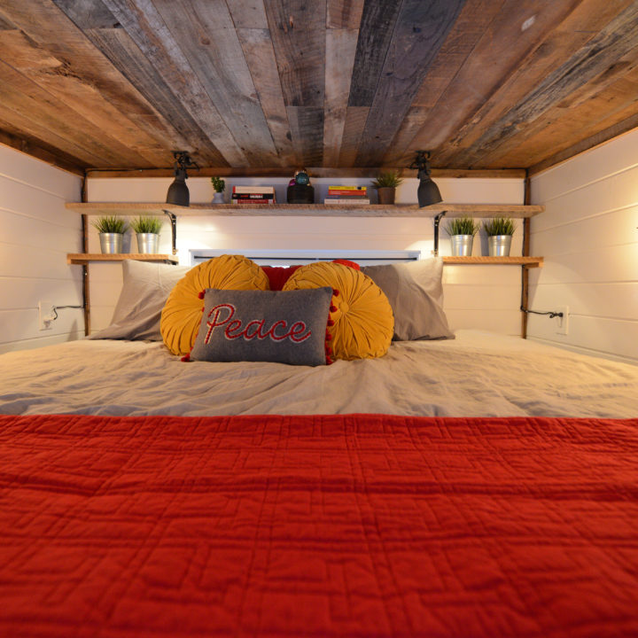 Loft bed in tiny home with charming lights and wooden ceiling with red comforter