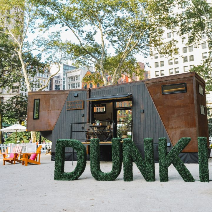 Tiny home with dunkin spelled out in grass in front