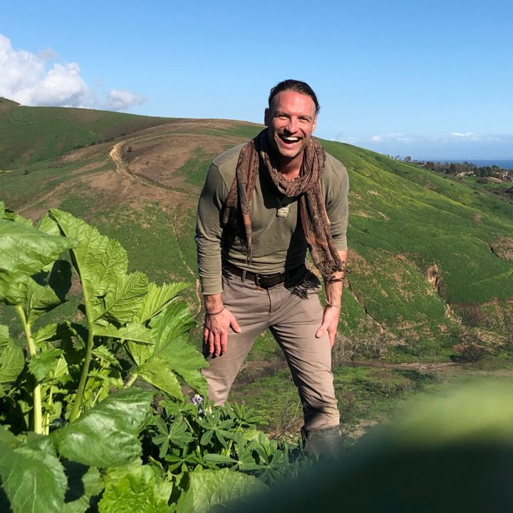 Laughing man in scarf standing in field with squash vines in foreground