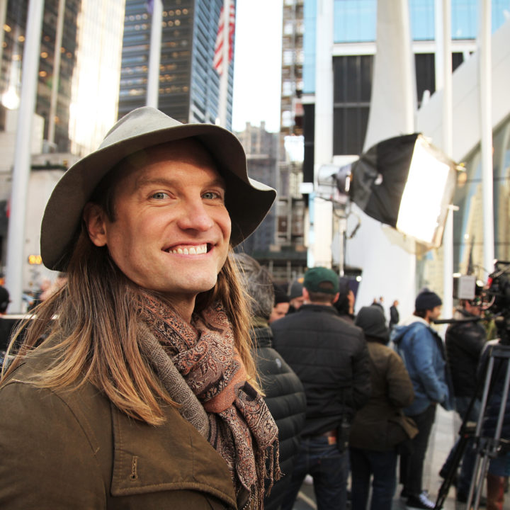 David Latimer in scarf and hat in front of city set