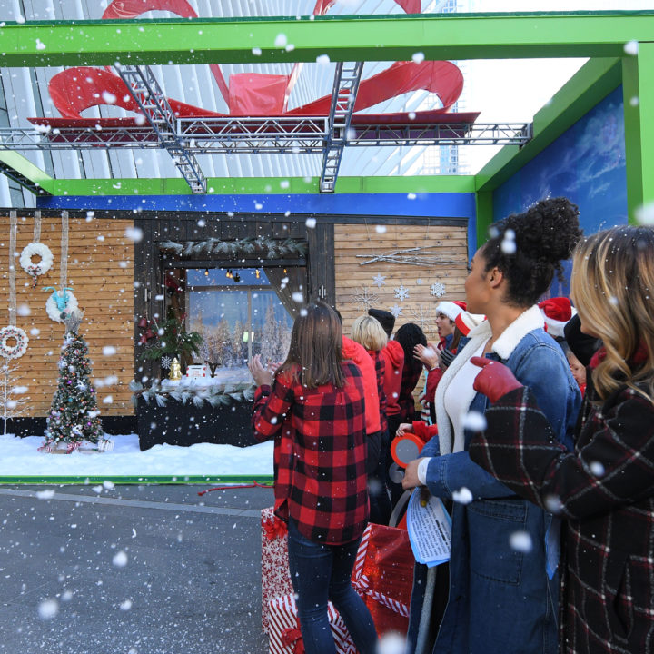 people in foreground of disney tiny home with fake snow falling