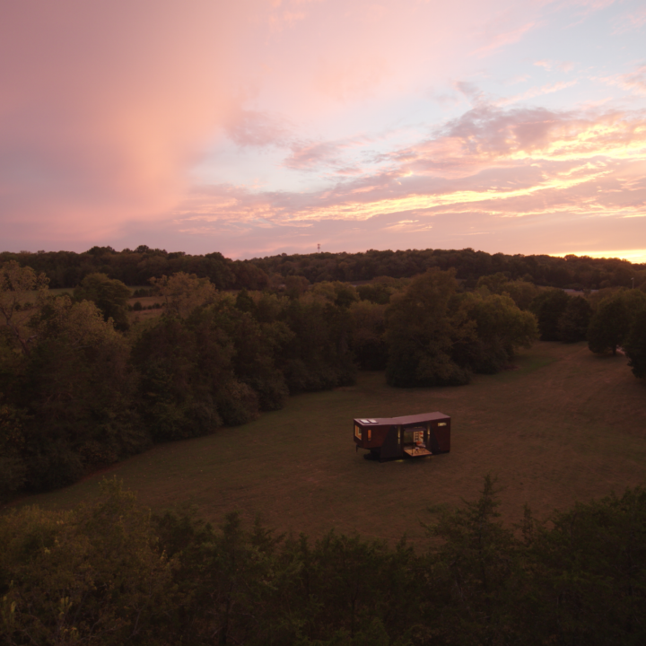 Tiny home from far away in a secluded clearing with sunset in background